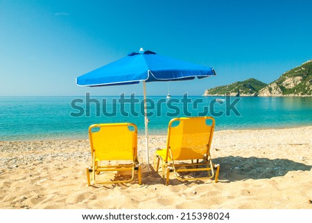 Yellow sunbeds and blue umbrella on a beautiful beach in Corfu Island, Greece Parasols and sunbeds into the sun on a tropical beach. - stock photo