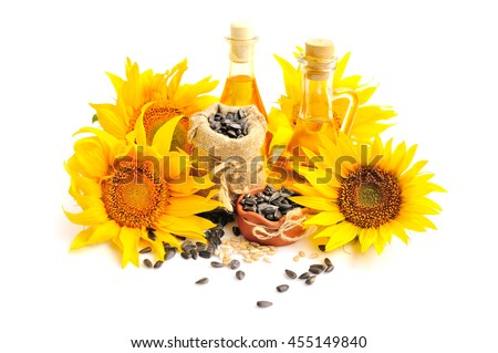 Yellow sunflowers with bottles of oil and a small bag of seeds on a white background - stock photo