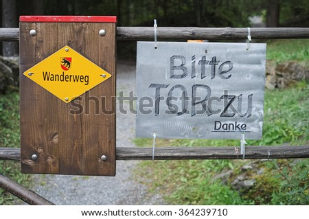 Yellow Swiss sign that reads footpath in German. A man made sign next to it asks people kindly to shut the door when entering.