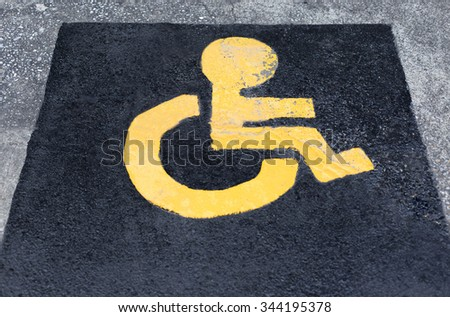 Yellow Symbol of Child wheel chair in parking lot - stock photo