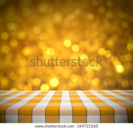 Yellow tablecloth on golden bokeh background - stock photo