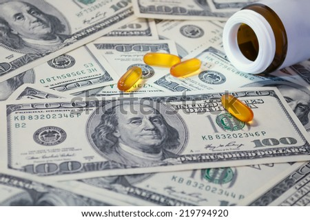 yellow tablet scattered on the bills of 100 dollars - stock photo