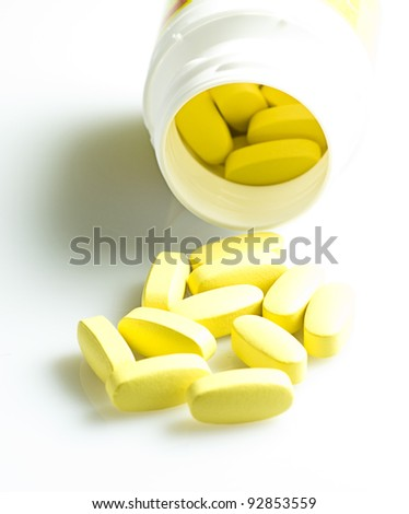 yellow tablets isolated on a white background - stock photo