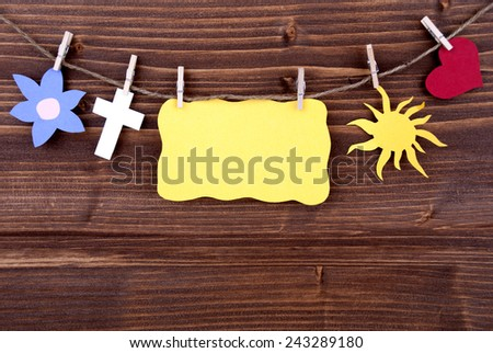 Yellow Tag Or Label With Heart And Flower And Cross And Sun On A Line With Copy Space Or Your Free Text Here On Wooden Background, Four Symbols, Vintage, Retro And Old Fashion Style - stock photo