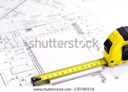 Yellow tape measure on architectural drawing - stock photo