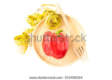 Yellow tape measure with fork and sweet red pepper in wooden plate on white background. Healthy lifestyle concept - stock photo