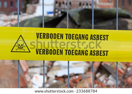 Yellow tape on fence with Dutch text 'no entry asbestos' in front of demolition site - stock photo