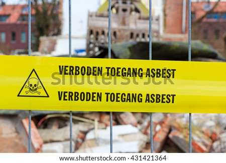 Yellow tape on fence with Dutch text 'no trespassing asbestos' in front of demolition site - stock photo