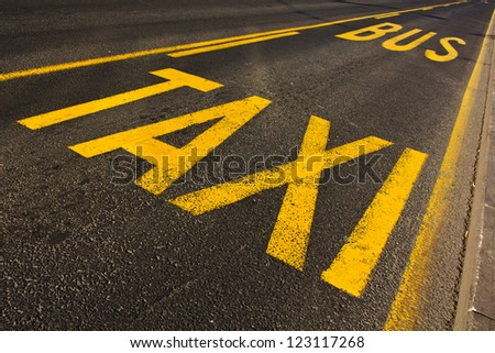 yellow taxi and bus sign painted on the street - stock photo