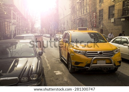 Yellow taxi crossing small street in Manhattan NYC