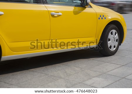 yellow taxi moves on the city street