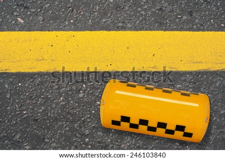 Yellow taxi sign lying on the road. Texture, background, concept - stock photo