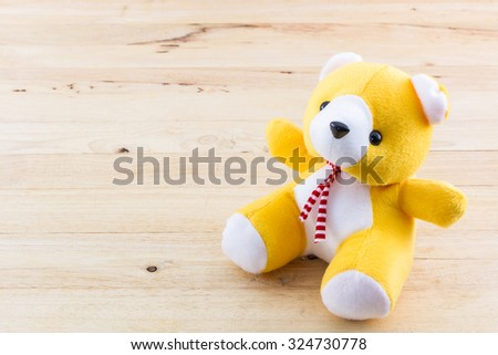 Yellow teddy bear toy on wood background. - stock photo