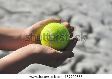 Yellow tennis ball, illuminated by the sun, in the hand of a child under the open sky.