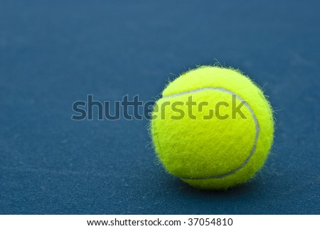 Yellow Tennis Ball on dark blue tennis court