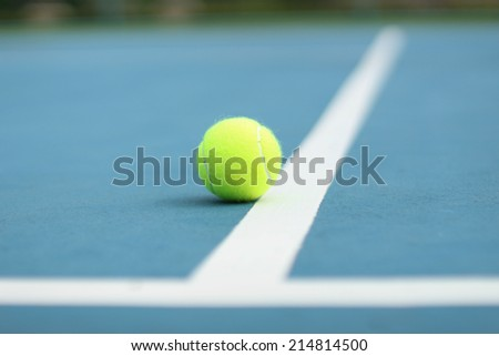 Yellow tennis ball on the blue courte