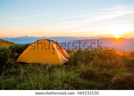 Yellow tent in the mountains, sunrise on the ridge, trekking, travel gear, expedition, tour, conductor