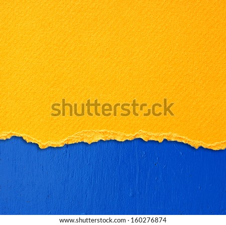 yellow textured torn paper over blue wall background