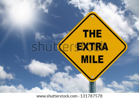 Yellow the extra mile road sign - stock photo