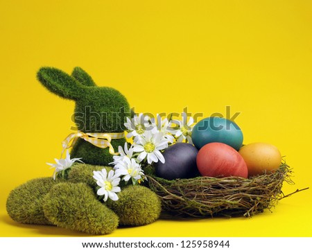 Yellow theme Happy Easter scene still life with grass bunny rabbit with rainbow color eggs in a nest with white daisies. - stock photo