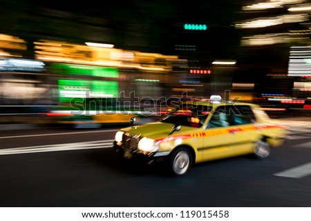 Yellow Tokyo taxi rushing through Tokyo downtown district at night. - stock photo