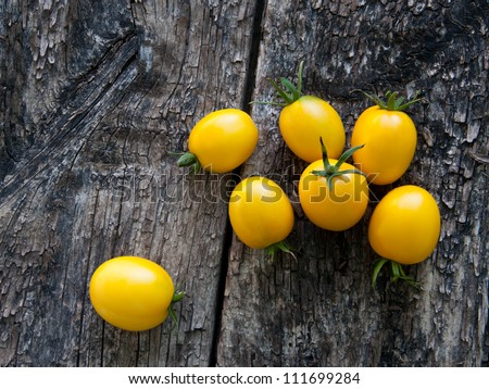 yellow tomatoes on a wooden background - stock photo