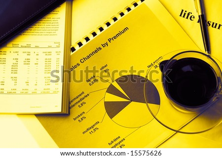 Yellow toned annual report with card-holder, documents and cup of coffee - stock photo