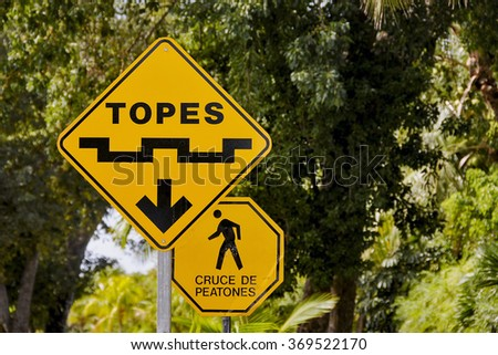 Yellow topes speed bumps warning traffic sign in mexico in front of green bushes - stock photo