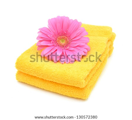 yellow towels and pink daisy flower closeup on white
