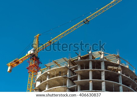 Yellow tower crane and building construction site against blue sky