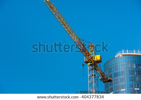 Yellow tower crane and modern high-rise building against blue sky - stock photo