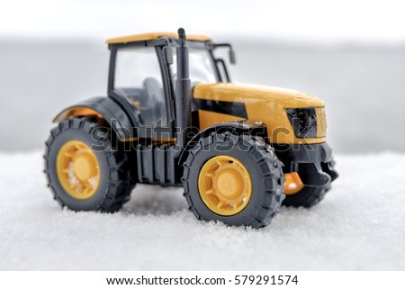 yellow toy tractor with large black wheels close-up, standing in the snow