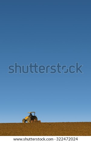 Yellow tractor driven by a farm preparing the soil for planting with white isolated background and copy space - stock photo