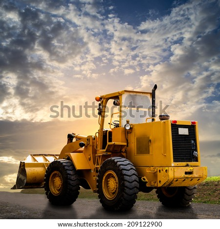 yellow tractor on the road with cloudy blue sky - stock photo