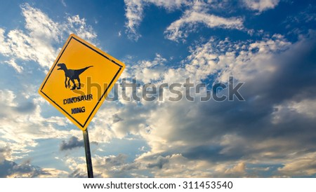 Yellow traffic label with dinosaur pictogram on sky background