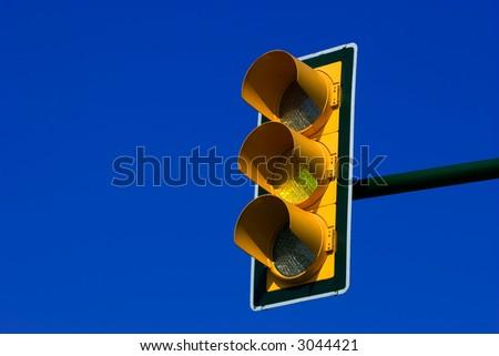 Yellow traffic light on blue sky - stock photo