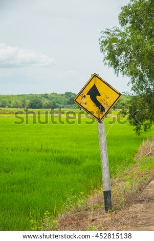 Yellow traffic sign on the side of the cornfield.