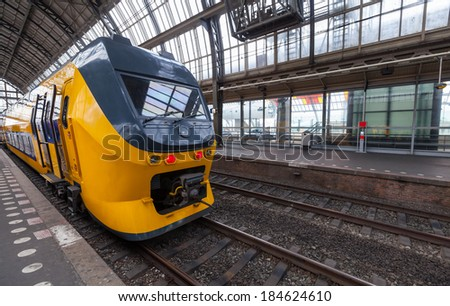 Yellow train stands on the central railroad station in Amsterdam - stock photo