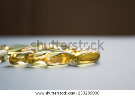 Yellow transparent capsules on gray table - stock photo