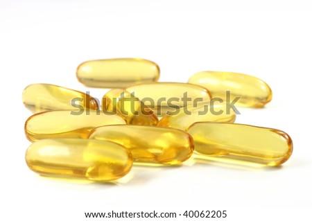 Yellow transparent pills of fish oil - stock photo