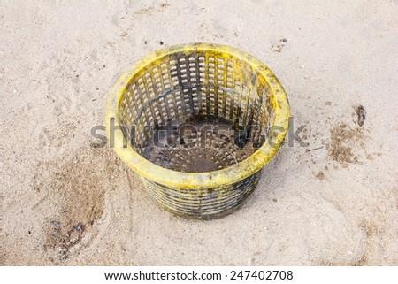 yellow trash basket on sand - stock photo