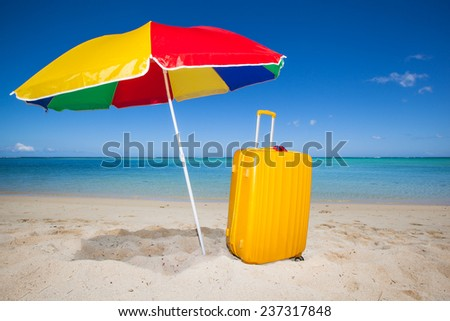 yellow trolley and a colorful sunshade in the white sand of a beautiful beach with a turquoise sea and a blue sky, Mauritius, Africa - stock photo