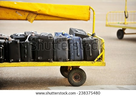 Yellow trolley loaded with luggage on an airport tarmac track - stock photo