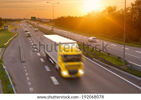 Yellow truck in the rush hour on the highway at dusk - stock photo