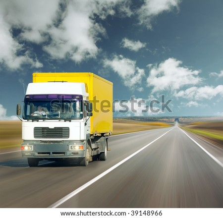 Yellow truck on road under blue sky - stock photo