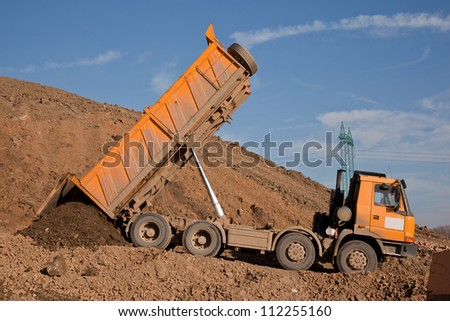 Yellow truck unloading earth material - stock photo