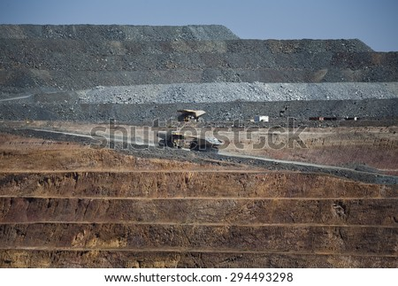 Yellow trucks drive out a dirt road in an open cast mine in New South Wales, Australia. Barrick Cowal Gold Mine. - stock photo