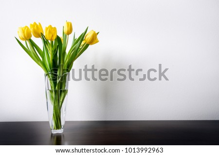 Yellow tulip in a vase on a wooden table and white wall. White copy space for a text. Top of view. Natural background. Valentines gift
