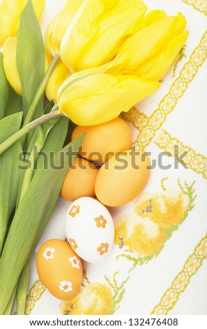 Yellow tulips and colored eggs on the embroidered cloth - stock photo