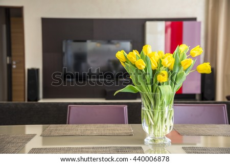 Yellow tulips in the vase on a table